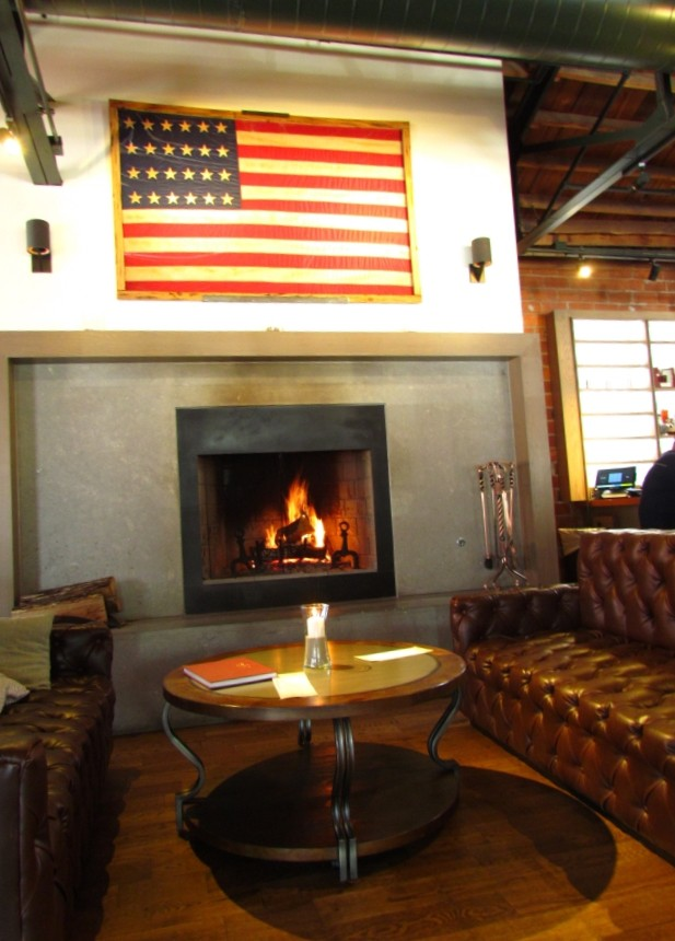 A historic American flag with 24 stars hangs above a welcoming fireplace. Guests can relax on the tufted brown leather couches that flank the round wooden table in this inviting seating area of the Third Street Social Restaurant.