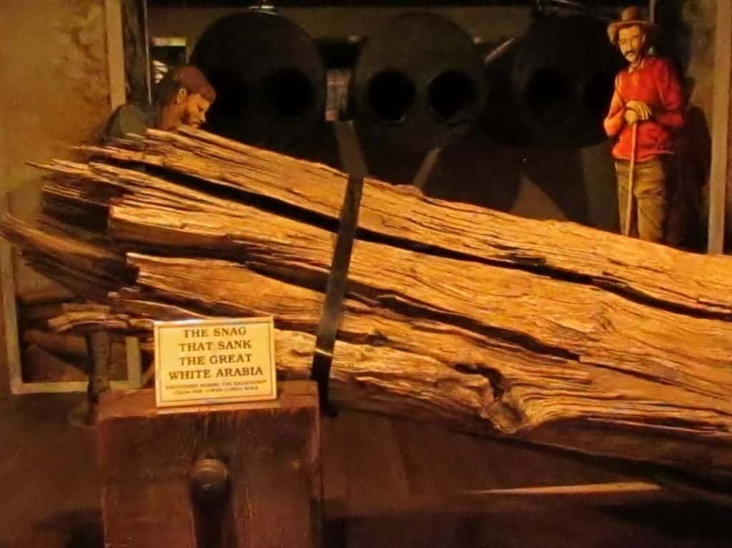 A large tree trunk is displayed as the object that caused the damage, which resulted in the sinking of the Arabia Steamboat.