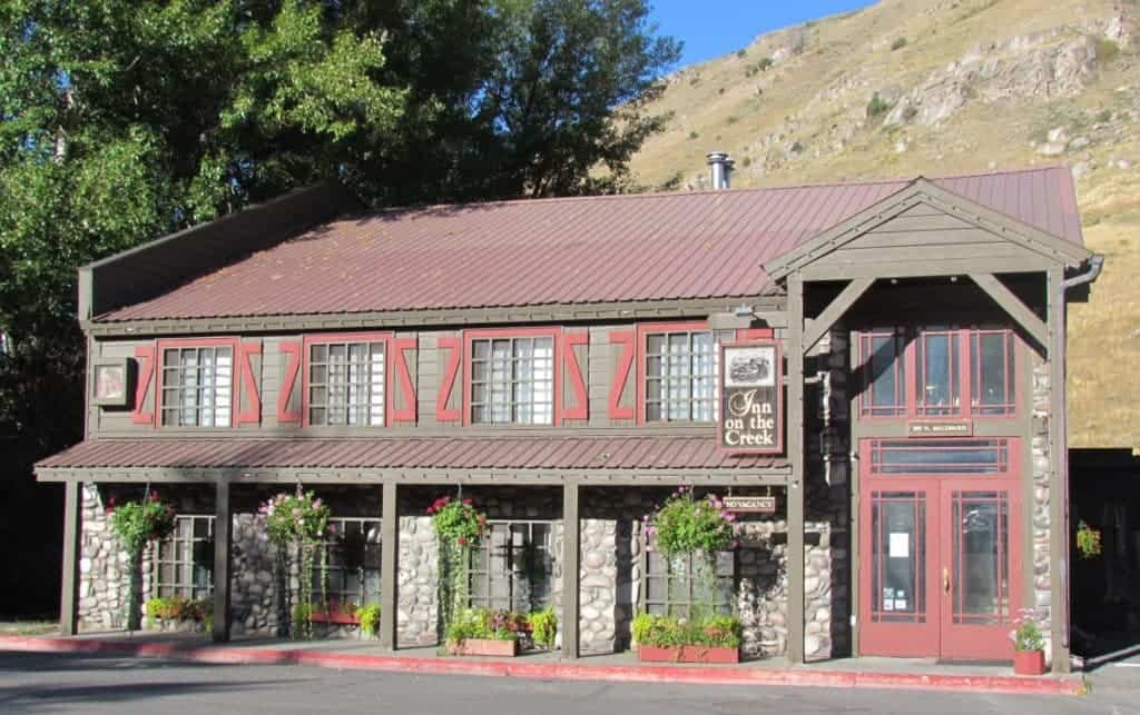 The stone first floor is capped with a barnlike second story wooden structure of the Inn on the River in Jackson Hile, Wyoming. Hanging plants and flower filled planters adorn the front of this quaint lodging option.