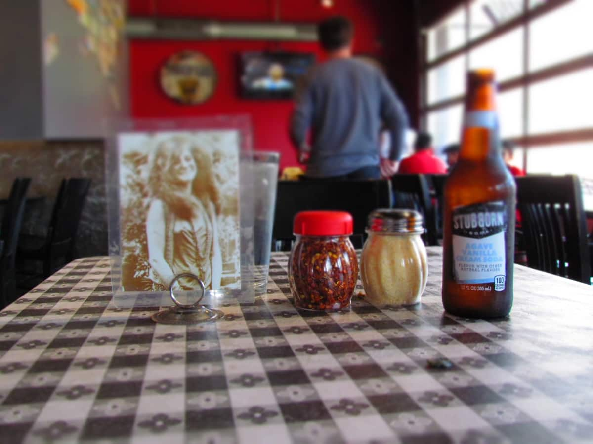 A photo of Janis Joplin is udsed to identify which customer's order is being delivered. It's holder rests beside jars of pepper flakes and grated parmesan cheese., as well as a bottle of soda. They all sit atop a checkered tablecloth in a pizza shop that is in a converted garage.