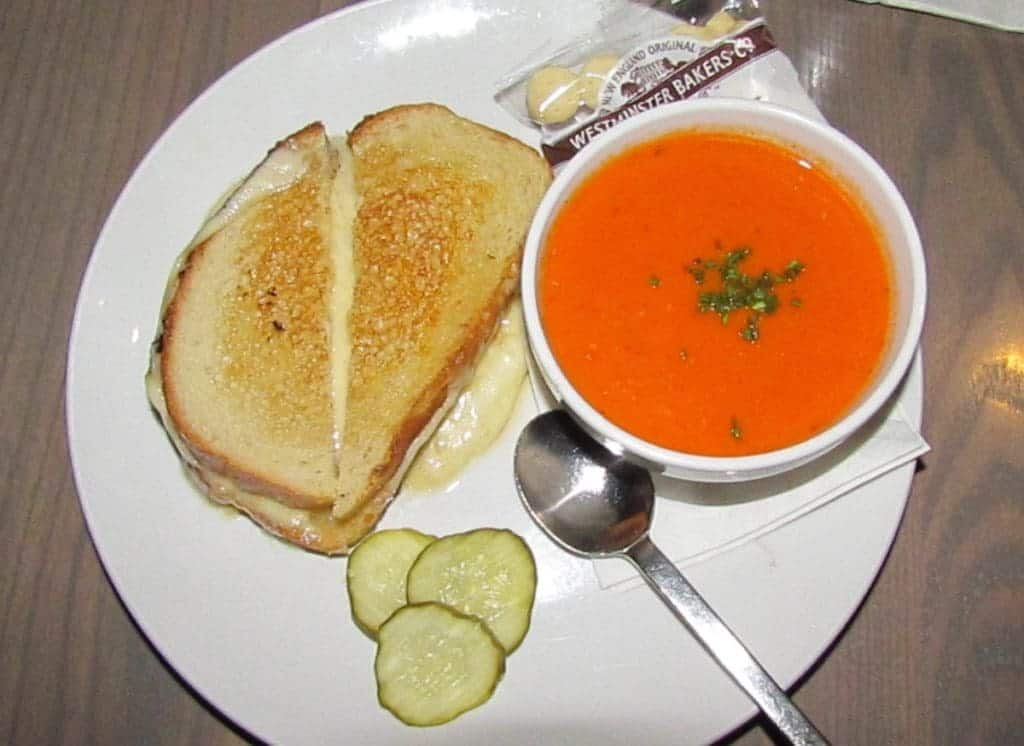 A white plate holds a dinner combination of grilled cheese sandwich, picle slices, and a bowl of tomato bisque. A package of oyster crackers and a spoon rest near the bowl.