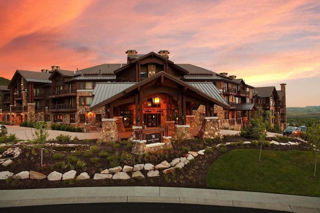 The large stone and wood lodge is the Waldorf Astoria Hotel in Park City, Utah. Rocks and greenery adorn the front lawn, as the waning sunlight casts red hues on the evening sky.