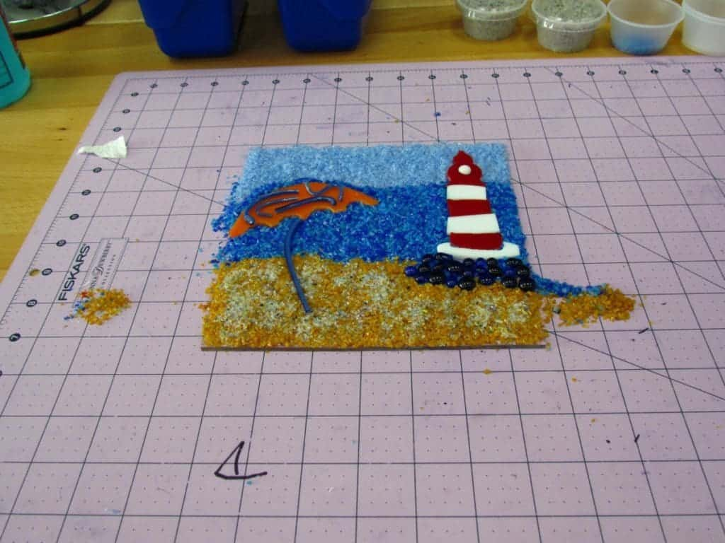 A lighthouse scene made with glass.
