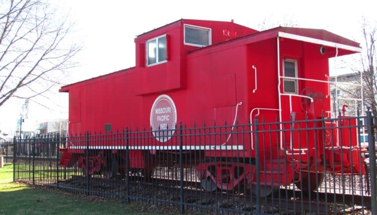 The bright red caboose sits near the Chamber office for Tourism in downtown Lee's Summit, Missouri. This iconic landmark signals to visitors that they are on Third Street.