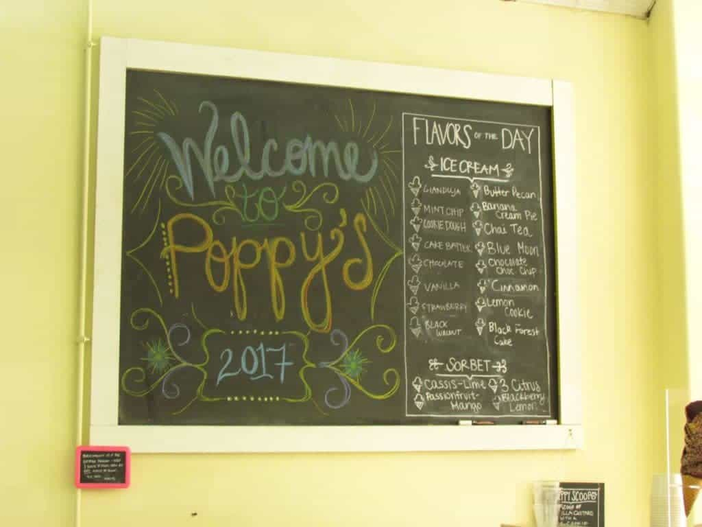 An oversized chalkboard is used for a manu board at Poppy's Ice Cream in downtown Lee's Summit. The board contains a list of the currently available flavors of ice cream and sherbert.