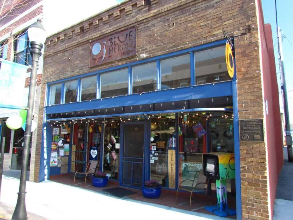 The bright blue trim of the Blue Heron store accents the brick consturction of the building. Large gwindows are filled with colorful items for sale.