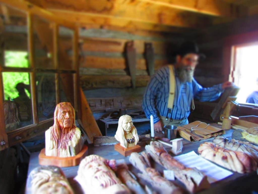 Wood carver sells his products.
