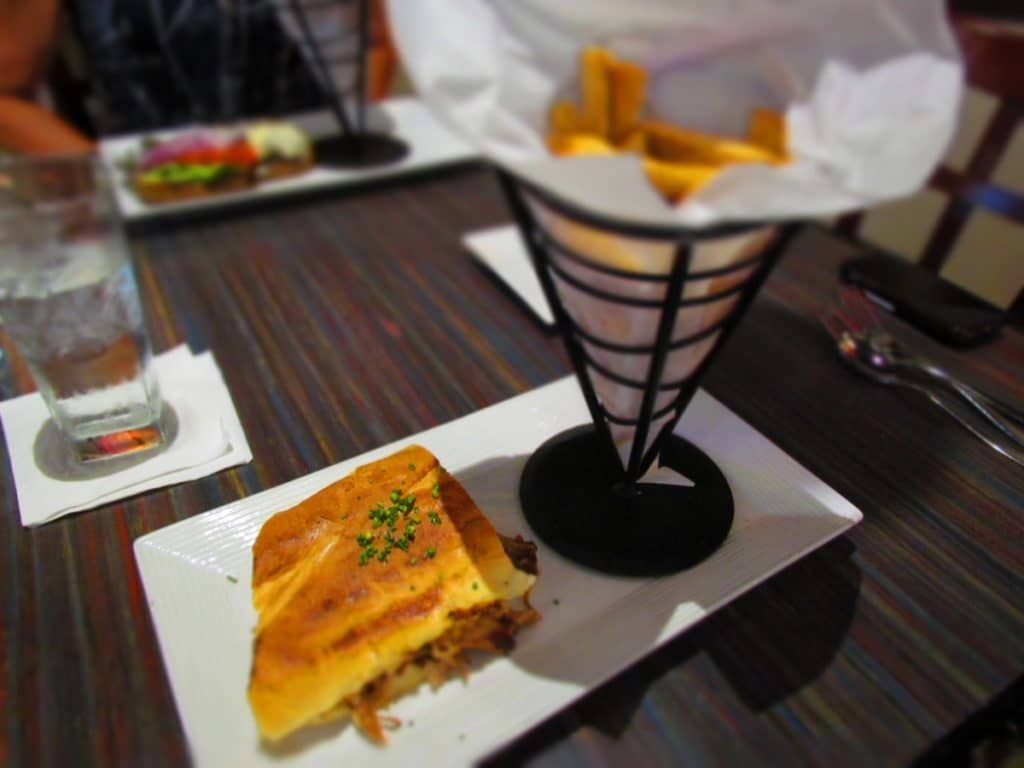 A plate filled with a Cuban sandwich and an order of french fries.