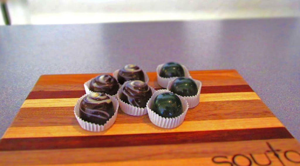 Samples of two varieties of artisan chocolates are served on a wooden tray.