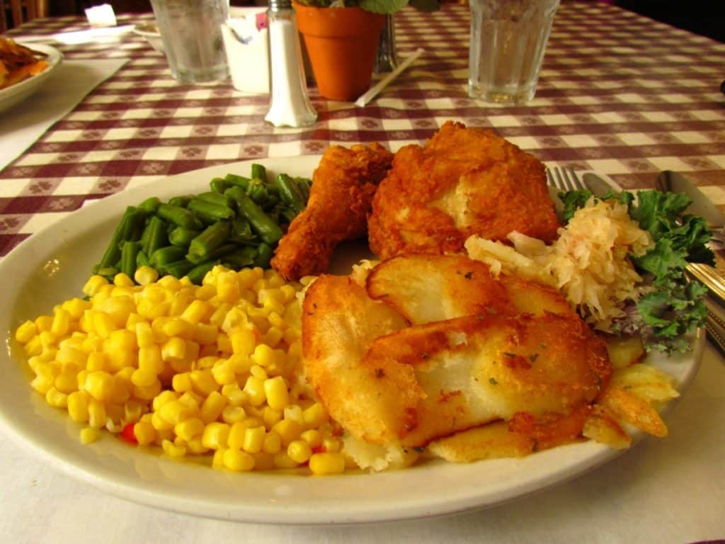 A plate of fried chicken with potatoes and vegetables.
