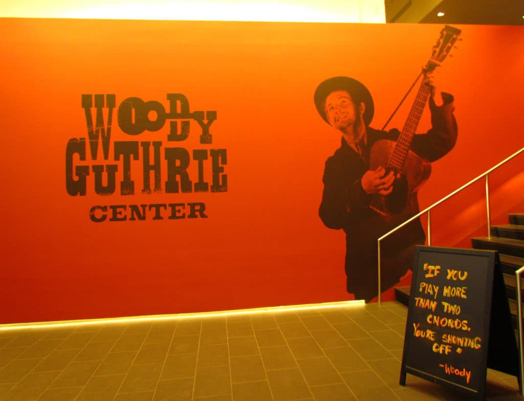 The entrance to the Woody Guthrie Center showcases a picture of the artist with his easily recognizable guitar.