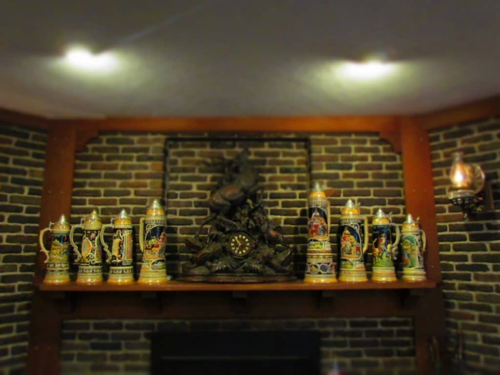 An over-sized mantel clock and various German beer steins adorn the wooden fireplace mantel.