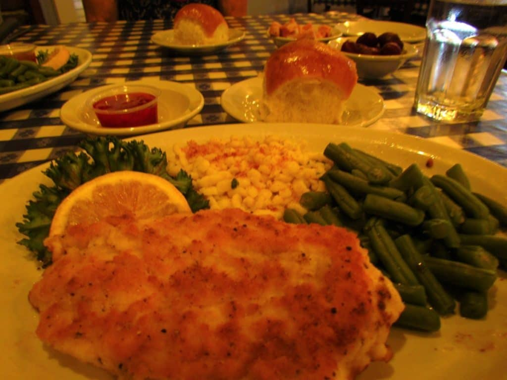 A dinner plate filled with Chicken Schnitzel, green beans, sweet corn, and served with a homemade roll with strawberry jam.