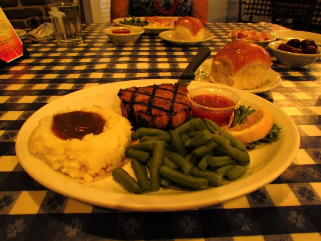 A dinner plate filled with Honey Apple Pork Loin, green beans, mashed potatoes with gravy, cranberry applesauce, and served with a roll and strawberry jam.
