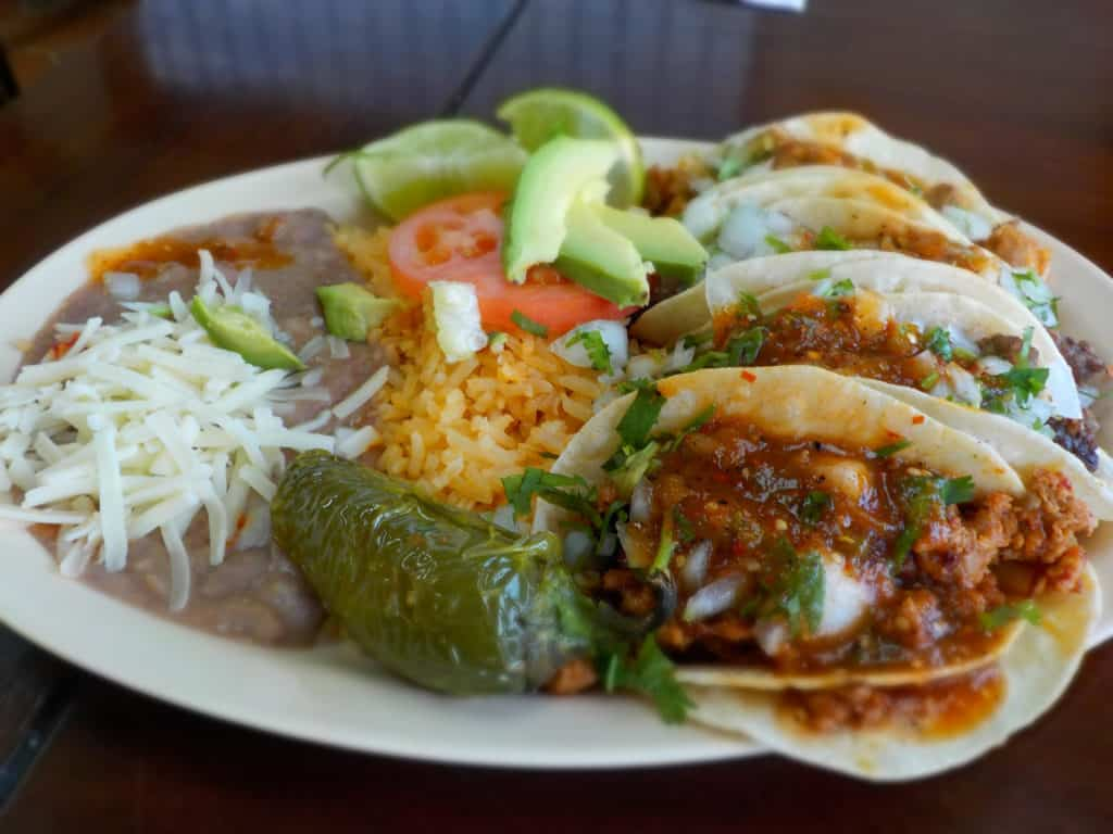 A plate filled with street tacos also holds refried beans and rice.