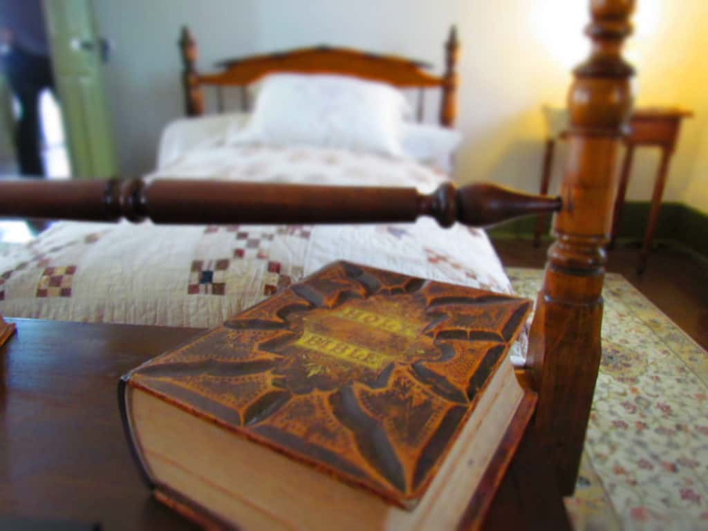 A bible rest on a chest at the foot of a bed.