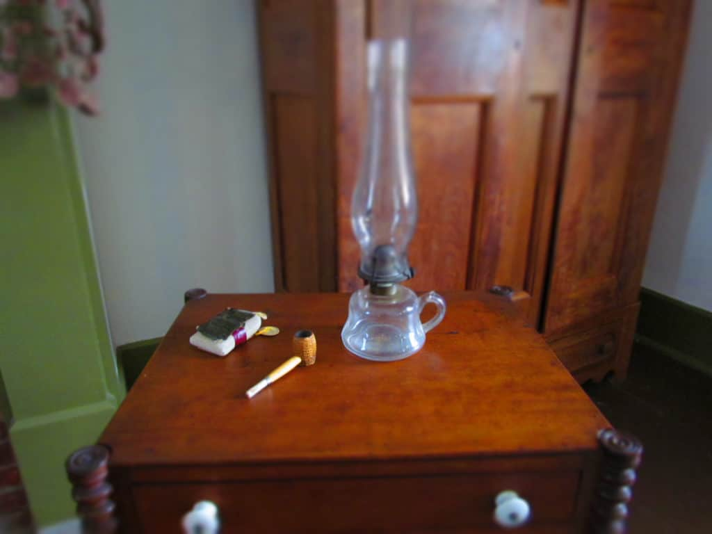 A pipe and tobacco rest on a table near the fireplace.