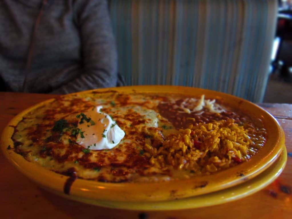 A steaming plate filled with chicken enchiladas, rice and beans.