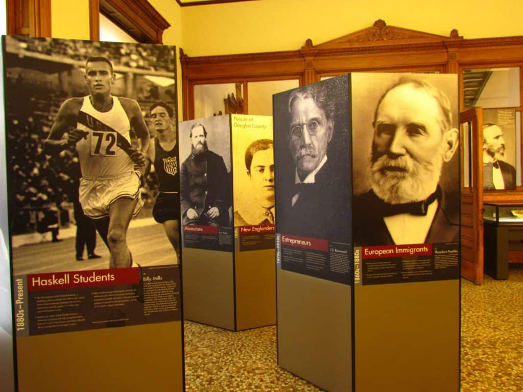 Over-sized standing placards reflect on the peopl and groups who helped shape the future of Lawrence, Kansas.