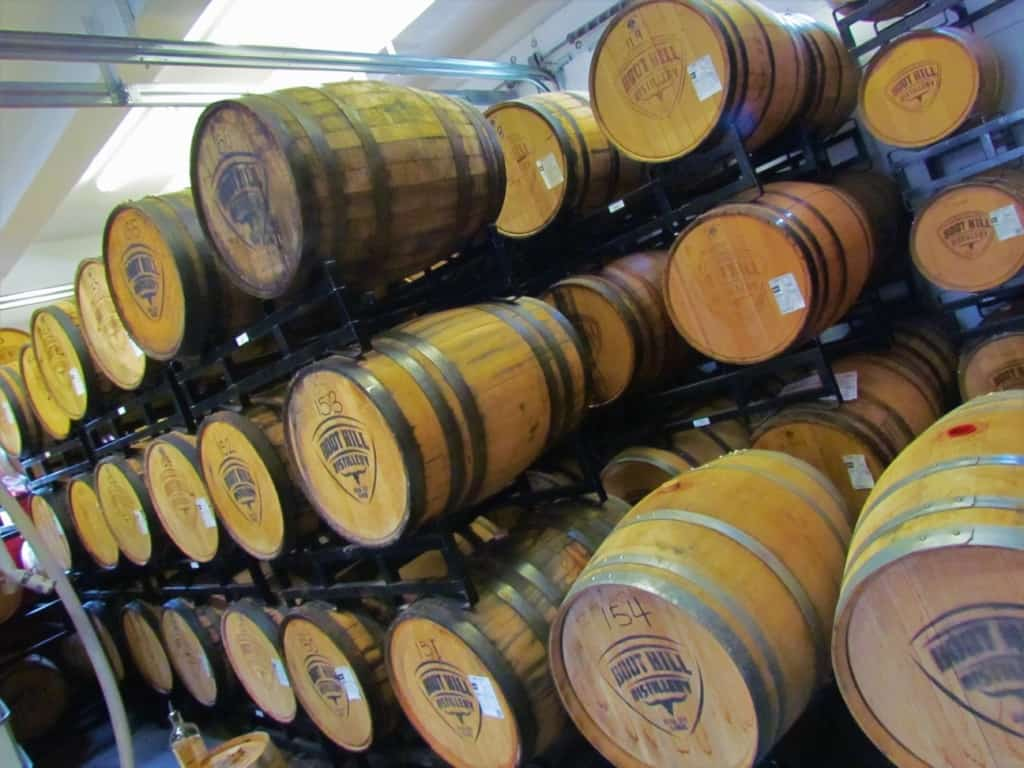 Charred oak barrels line the wall as the whiskey ages.