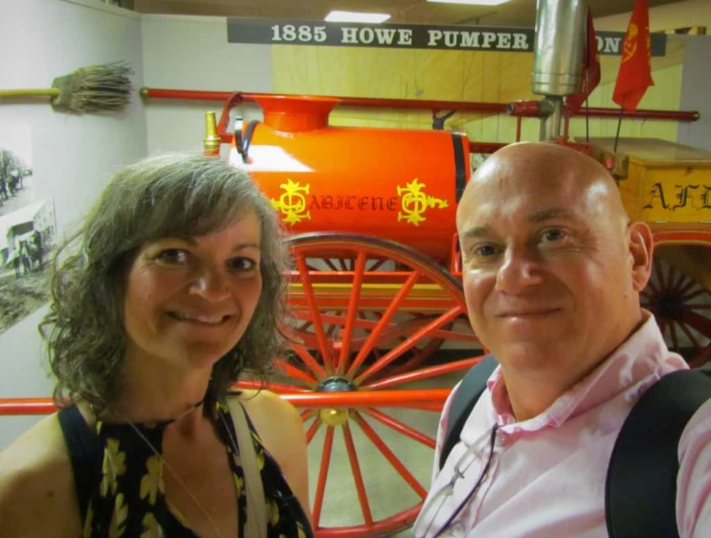 The authors pose for a selfie in front of an old piece of fire fighting equipment.