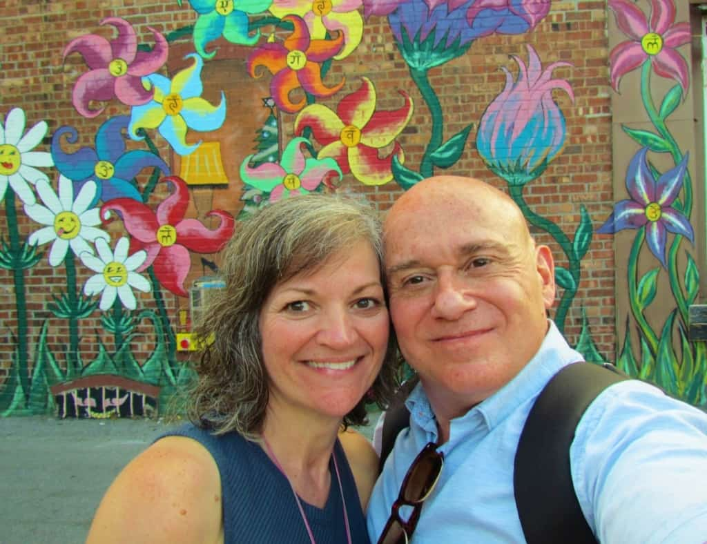 The authors pose in front of one of the many murals that can be found in downtown Des Moines.