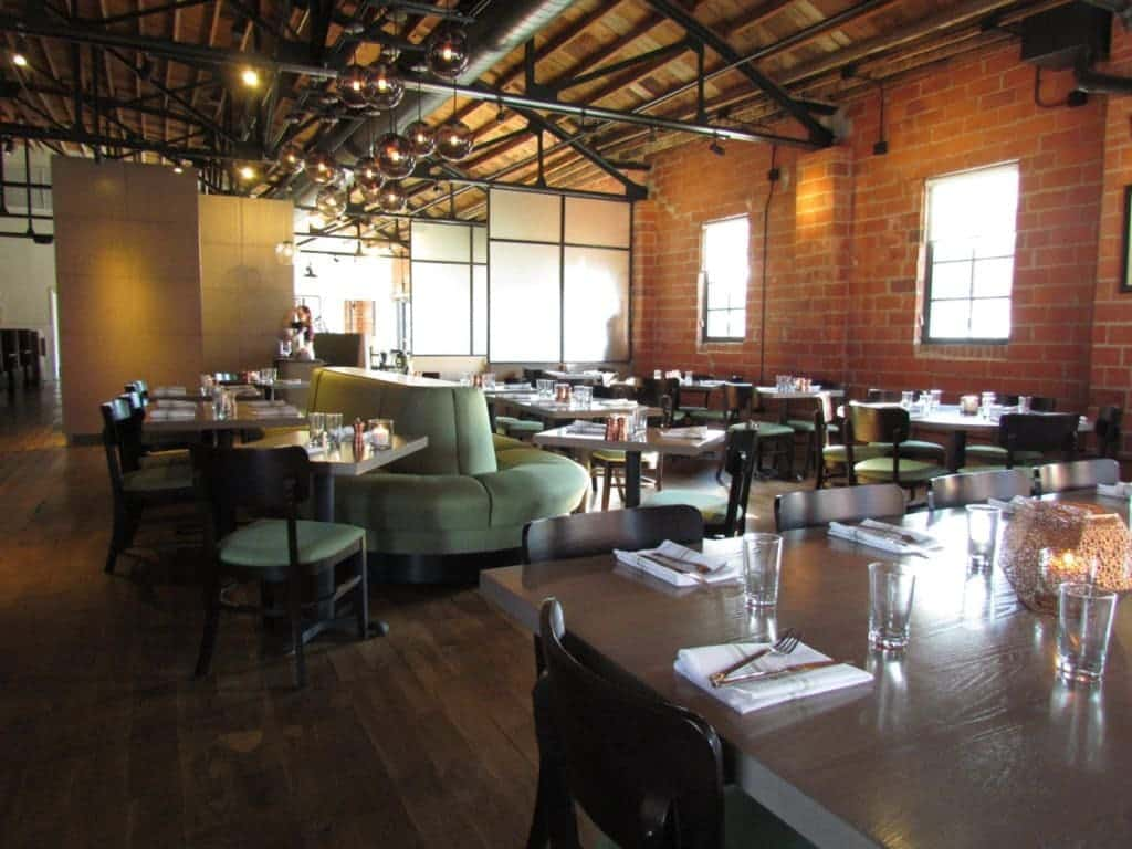 Stark tables and plush booth seating offer the seating options at Third Street Social. High wood beam celiengs rise above the indutrial style interior.