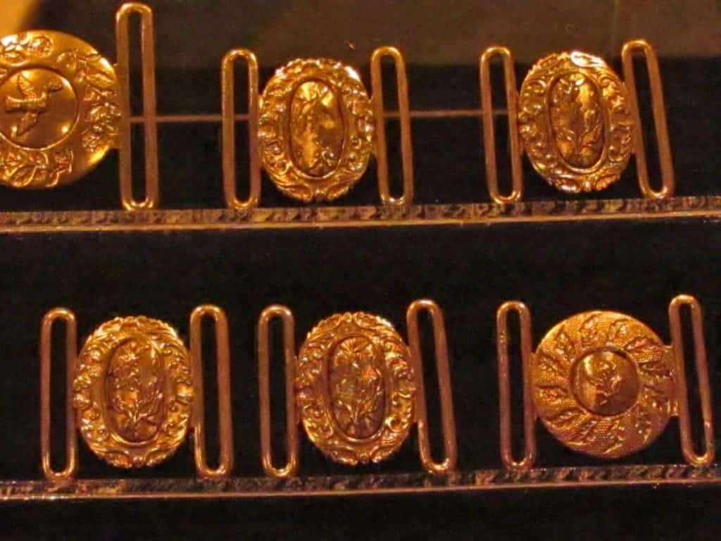Golden buckles are displayed as part of the items recovered from the wreckage.