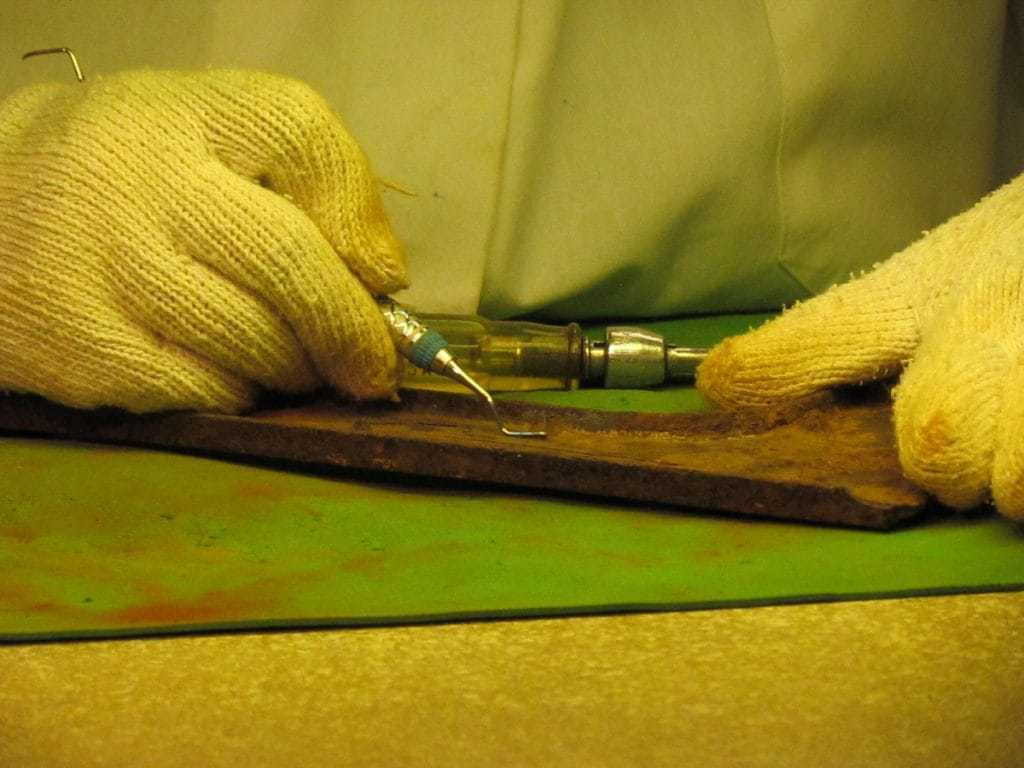 the gloved hands of a restoration worker handle a small cleaning device they use to scrape an artifact.