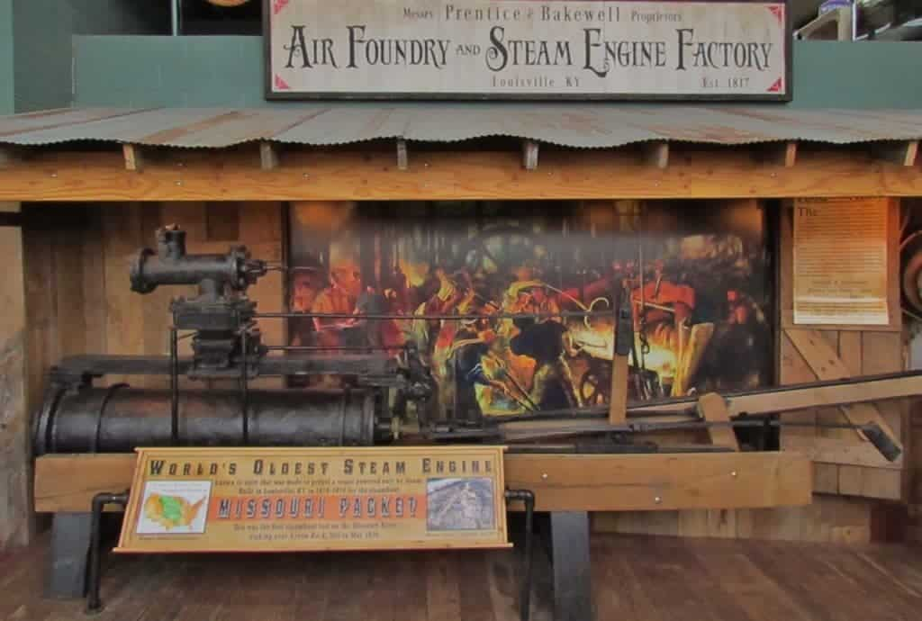 """A large metal steam engine is displayed along with a sign denoting it as the """"World's Oldest Steam Engine""""."""