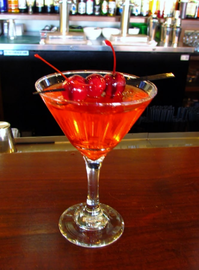 Three bright red skewered maraschino cherries rest on the rim of a martini glass. They are drizzled with choclate sauce, and hover above a red colored drink that tastes like a chocolate covered cherry candy.