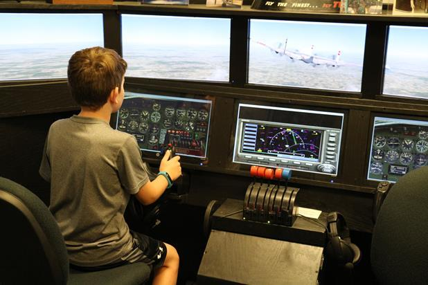 A boy tests his skills on a flight simulator.