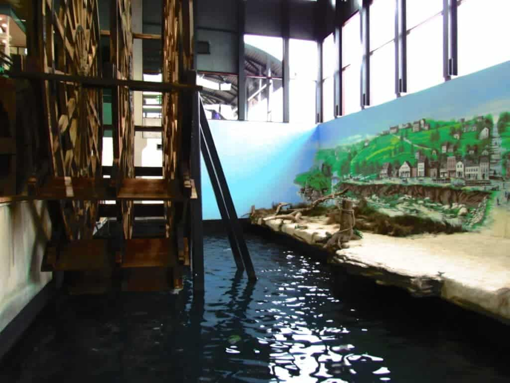 A large wooden paddle-wheel is displayed in a recreation of a riverbank scene.
