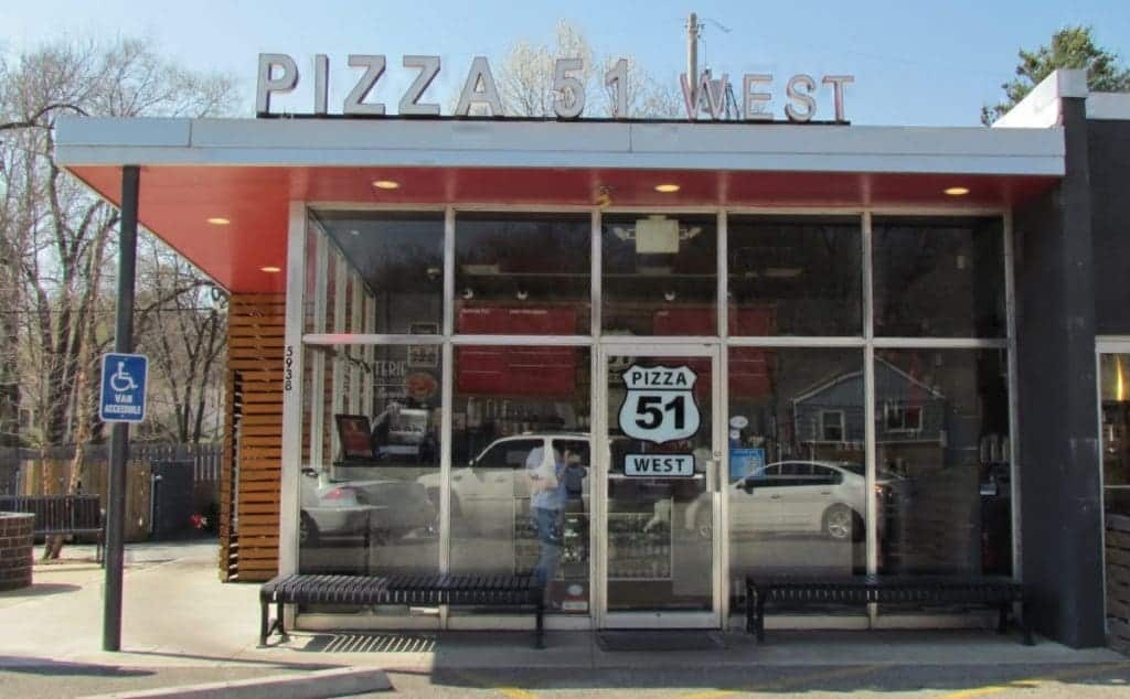 The main entrance to Pizza 51 West sits inside a glass front area of a converted 1950's gas station.