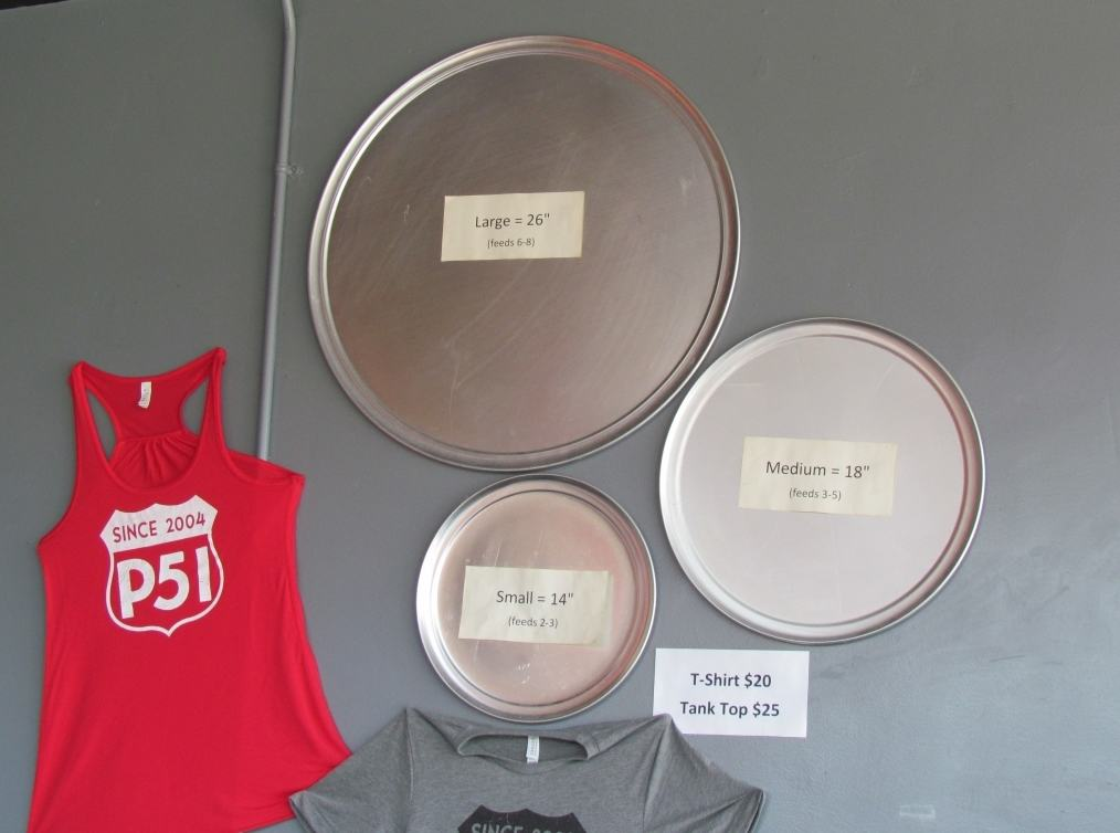 Silver pizza pans hang on the wall beside two P51 logo t-shirt options that can be purchased by guests.