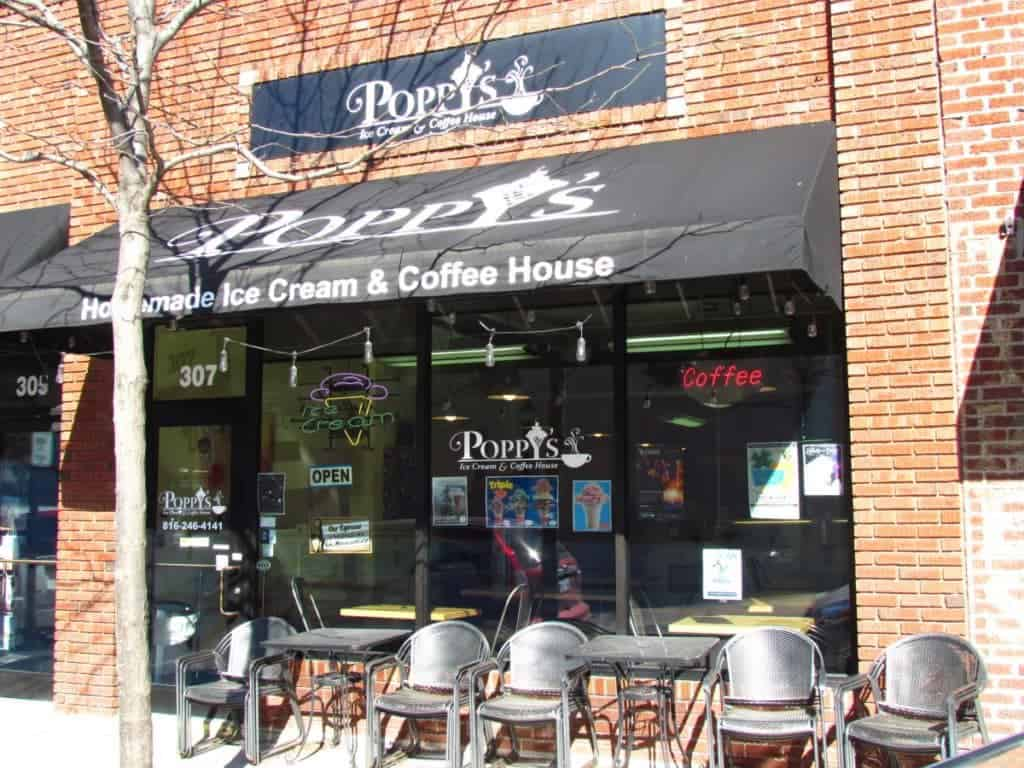 The exterior of Poppy's Ice Cream is a small glass front area topped with a black awning. A couple of metal tables with matching chairs offer customers a place to rest on warm weather days.