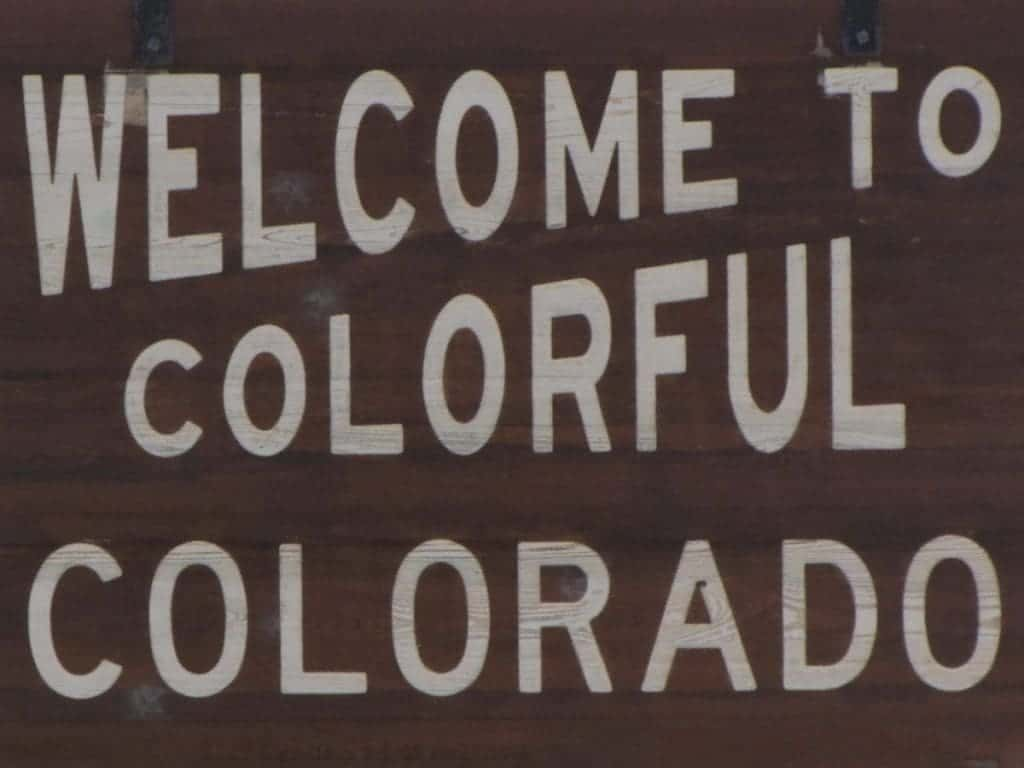 "Bright white stenciled letters on a dark brown sign denote to travelers ""Welcome To Colorful Colorado""."