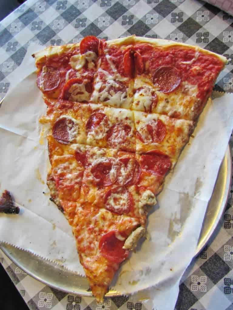 The oversized slice of pepperoni pizza rests on a sheet of parchment paper atop a 12 inch pie pan. The bright red sauce and meat slices add color to the yellow cheese and crust.