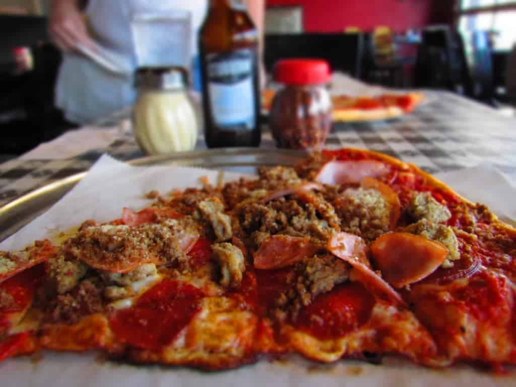 A closeup side view of the Pizza 51 West meat lovers pizza highlights the reds and browns of the meats in stark contrast to the tellow cheese. Behind these sit out of focus jars of pepper flakes and grated parmesan, as well as a bottle of soda.
