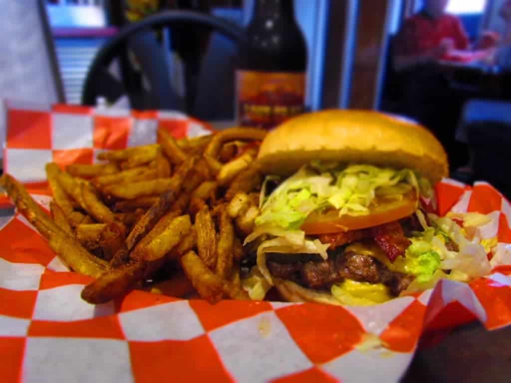 The grass fed burgers are piled high with lettuce, pickles, and tomatoes. Spicy french fries round out the basket of food in one of Tay's Burger Shack's value meals.