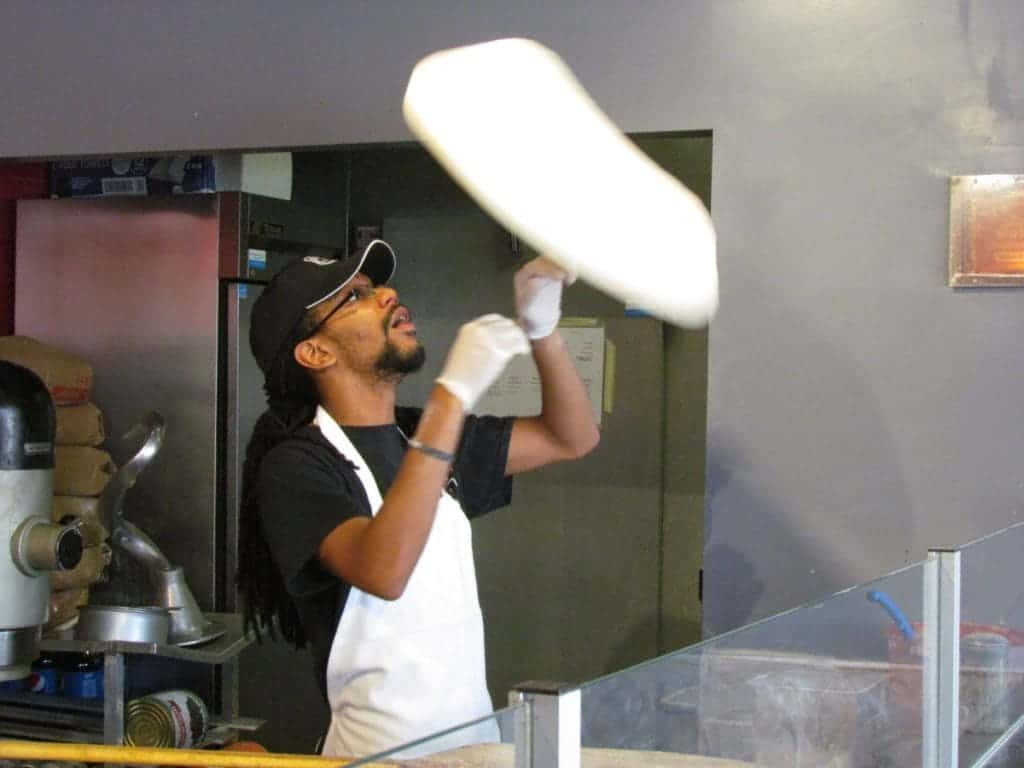 A Pizza 51 worker tosses dough to create the appropriate size and thickness for a pizza pie.