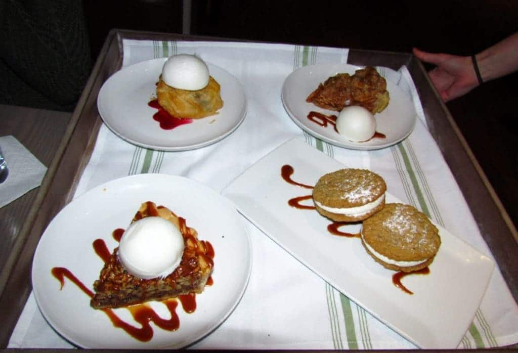 A tray holds an assortmenyt of dessert options. Pecan pie is drizzled with caramel sauce and topped with a dollop of ice cream. Twin Whoopie Pies rest on a caramel drizzle, and are sprikled with powdered sugar. A slice of baked apple pie rests beside a scoop of ice cream. A fruit filled croissant sits on a drizzle of fruit puree, and is topped with a scoop of ice cream.
