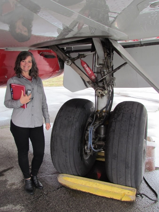 The landing gear of an airplane compared to an avergae human's height.