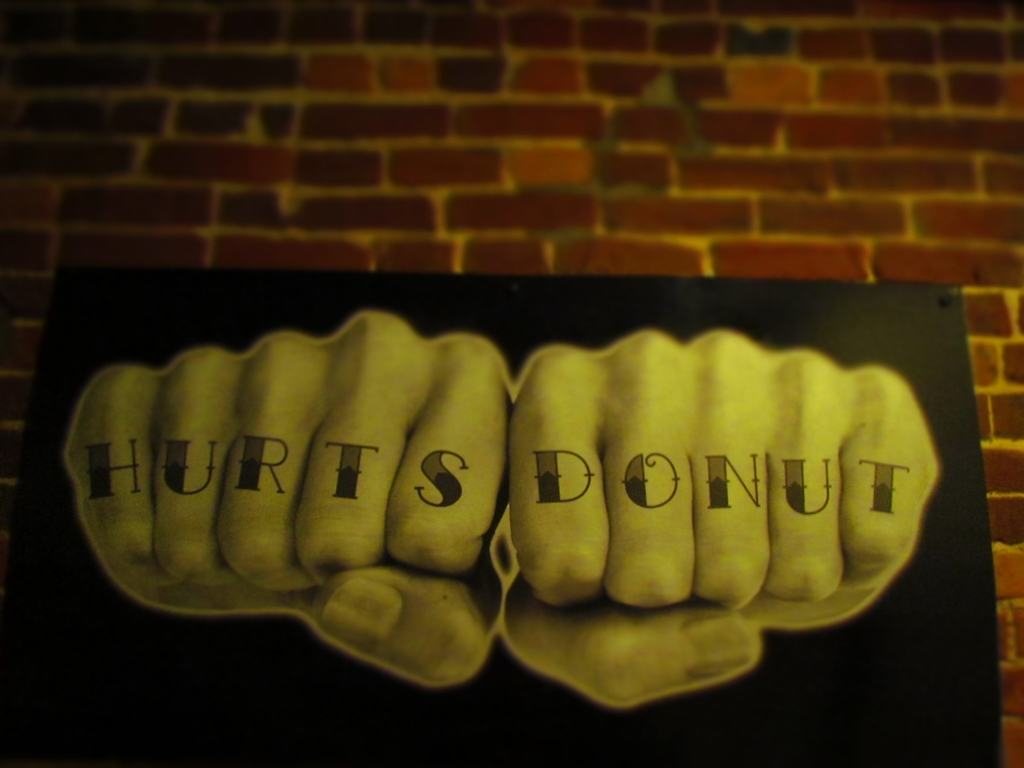 Hurts Donut sign with knuckles.