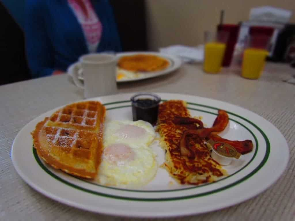 Waffle with eggs, bacon, and hash browns.