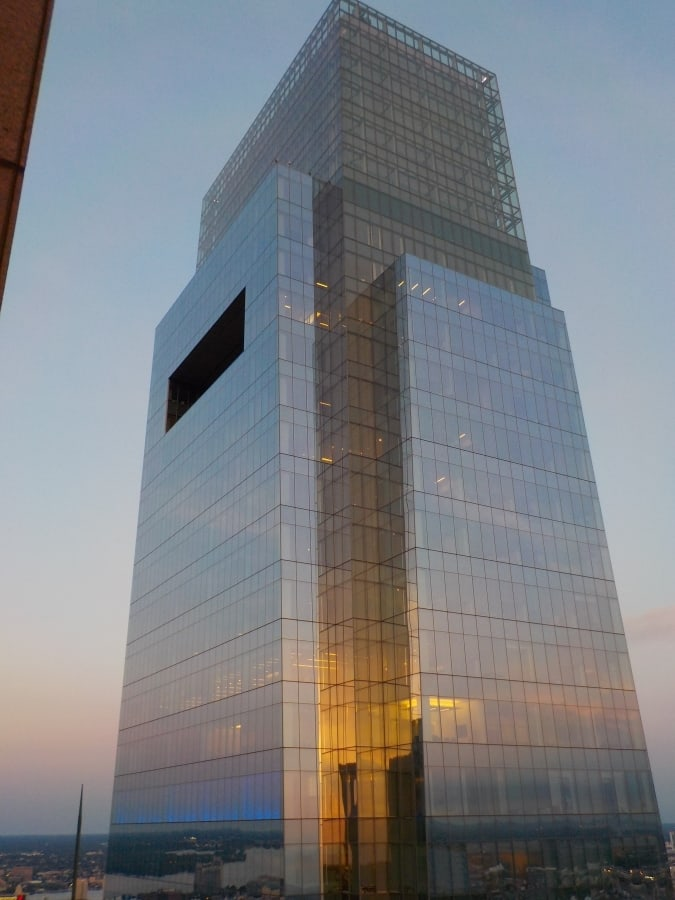 Sunset glows on a glass sided skyscraper.