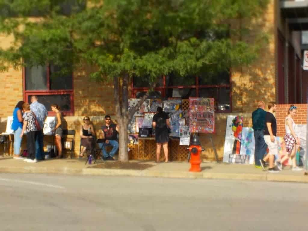 Local artists sell their art on the sidewalk.