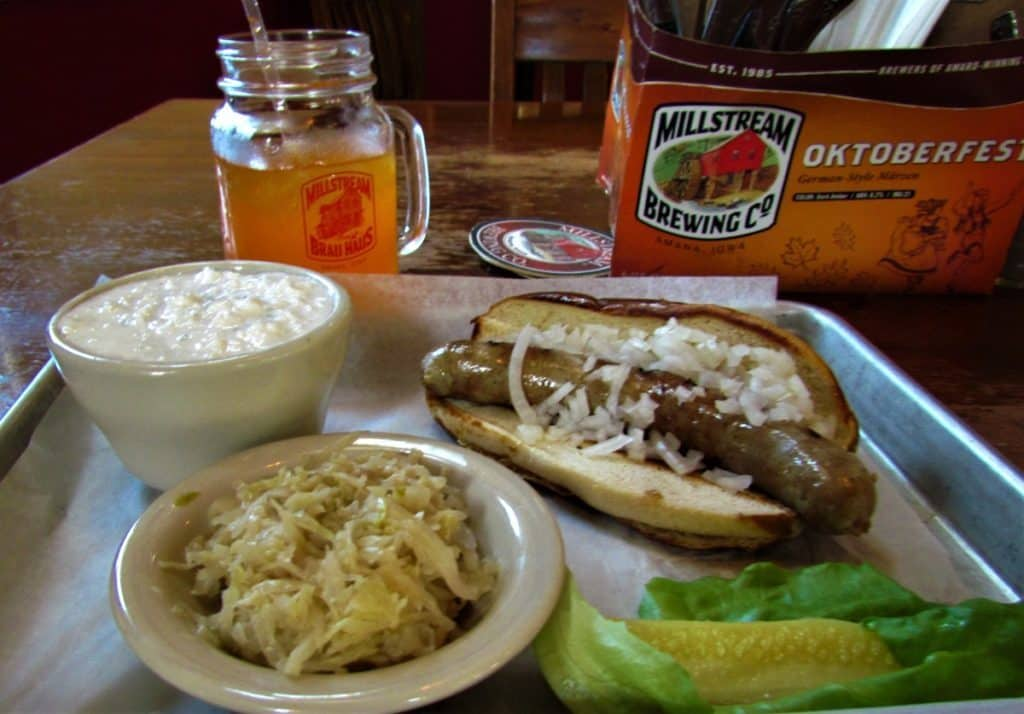 A German Bratwurste is served with fresh sauerkraut. The meal is accompanied by a bowl of cottage cheese, and a mug of orange soda.