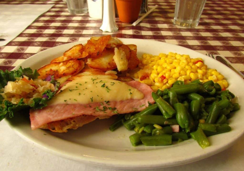 A ham and Swiss covered chicken breast with potatoes and vegetables.