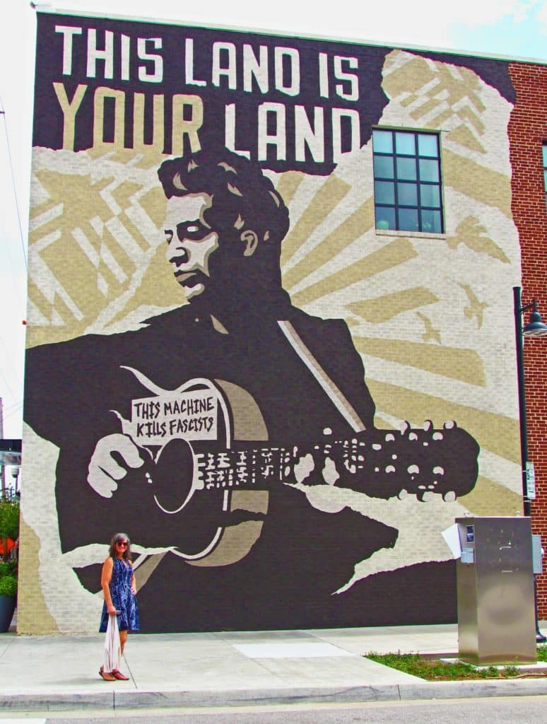 Crystal takes a moment to pose in front of the iconic mural on the side of the Woody Guthrie Center in Tulsa.